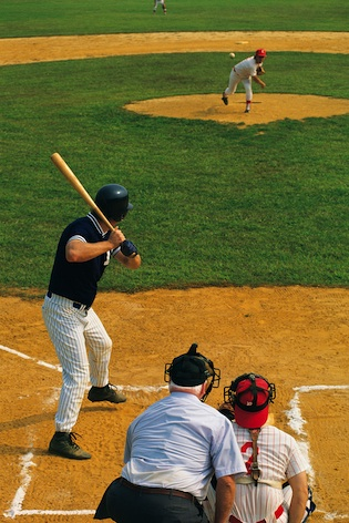 The pitcher pitches the ball. The referee and the catcher are behind the batter. ©iStock