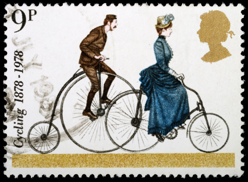 A penny farthing bicycle on the left, and a later two-wheeled bicycle with a chain to the right. Getty Images