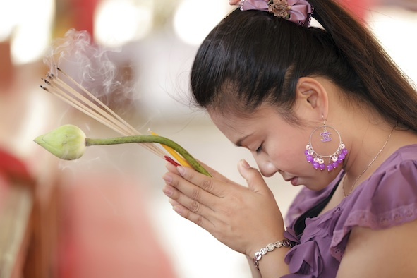 A Thai woman at a temple. She has incense sticks and a lotus bud. Getty Images