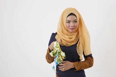 A Malaysian woman holding some ketupat. ©iStock