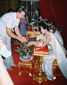 A wedding guest pours water over the bride and groom's hands for luck