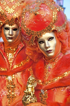 Some people dressed in fancy costumes and wearing masks in Venice at Carnevale