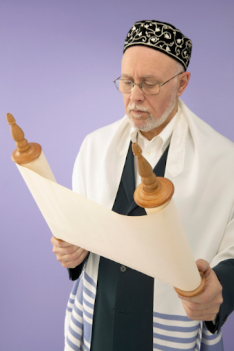 A rabbi reading from the Torah. He is wearing a prayer shawl. Photo©iStock