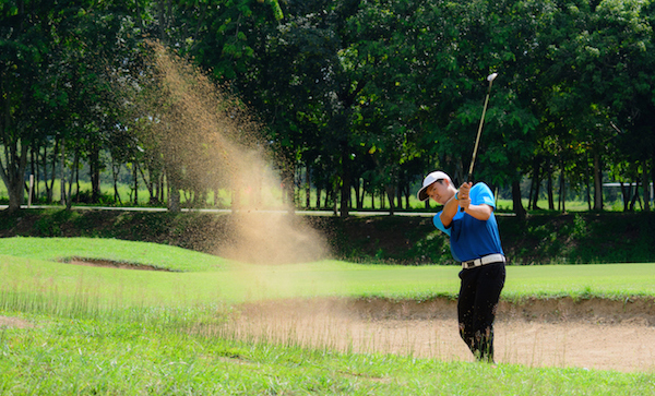 The golfer is trying to hit the ball out of the sand trap with as few strokes as possible. ©Getty