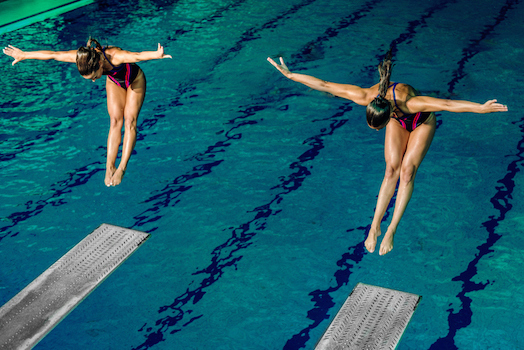 Divers leave the springboard and enter the water at the same time in synchronised diving. ©iStock