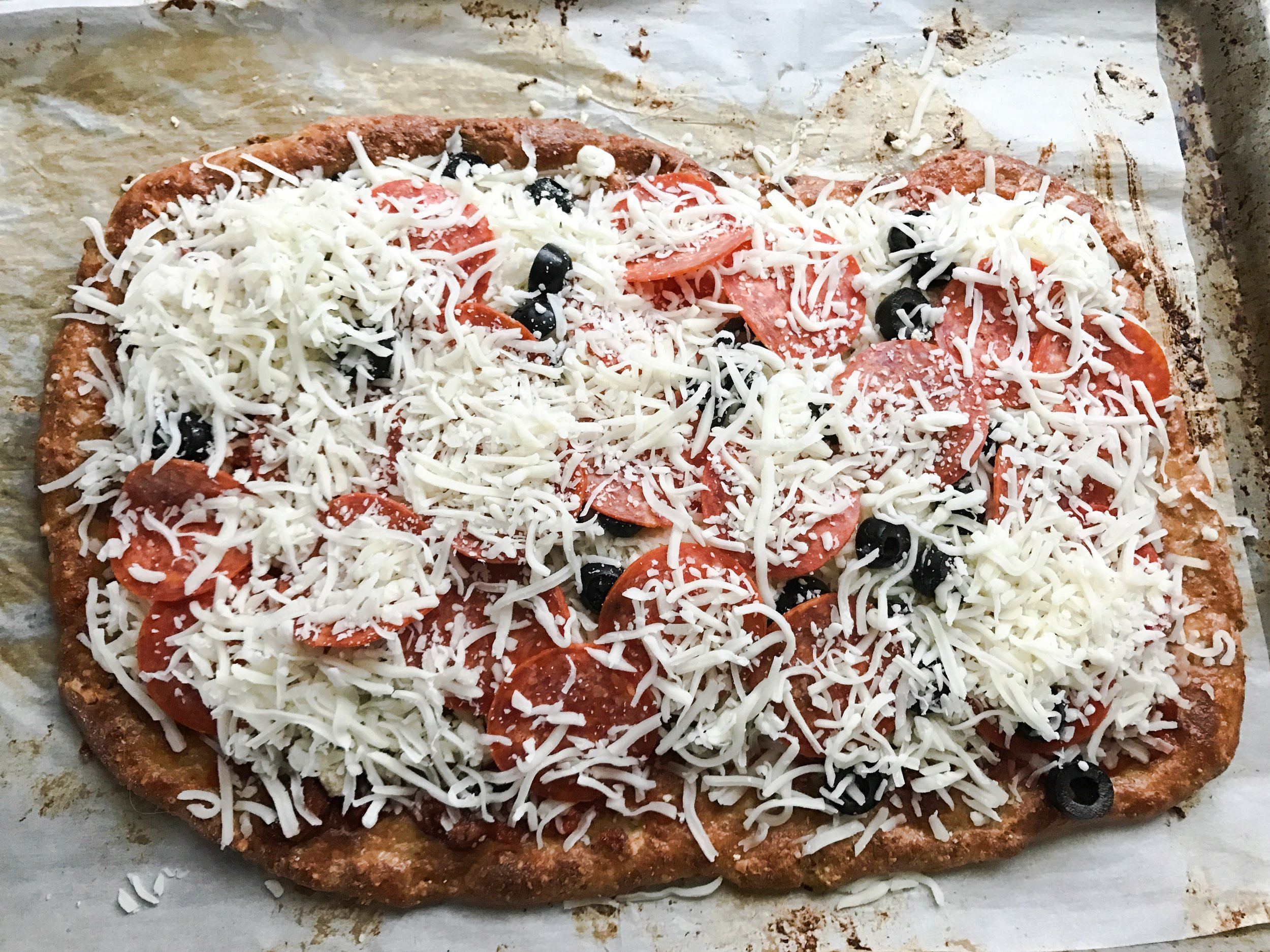 I forgot to take a picture of the crust baked. Ooops! Once crust is golden brown, take it out and add your sauce and toppings. I used Puttanesca Sauce on bottom, then a layer of shredded Mozzarella, then grated Parm, then sliced black olives, then Pepperoni, and then more cheese! I used an entire 16oz bag of shredded Mozzarella cheese by the time I was done between the crust and the toppings.