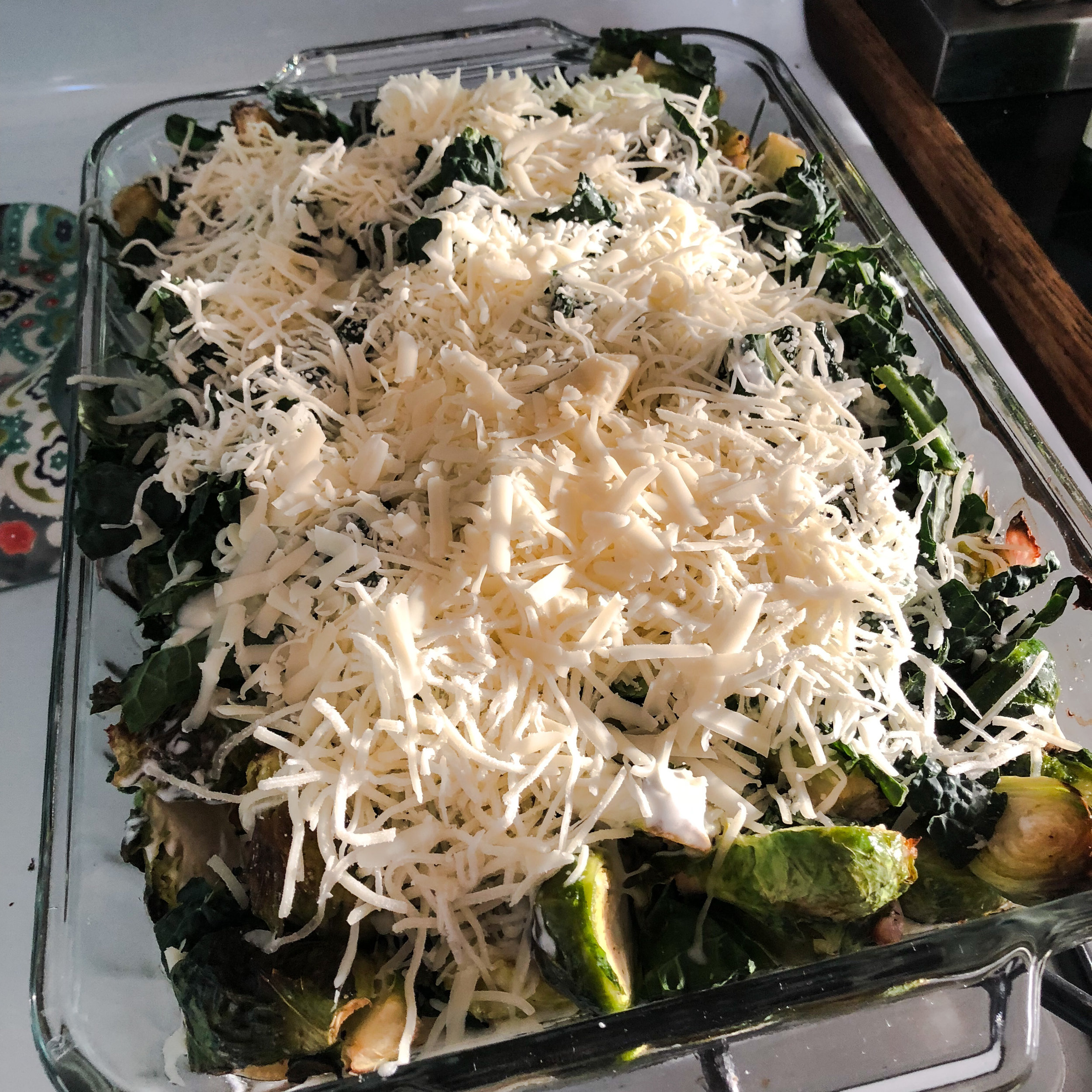 On top of kale add 1 1/2 cups of heavy whipping cream. Then add lots of shredded cheese! 1/2 cup of fontina cheese, 1 cup of mozzarella, 1/2 cup of gruyere.