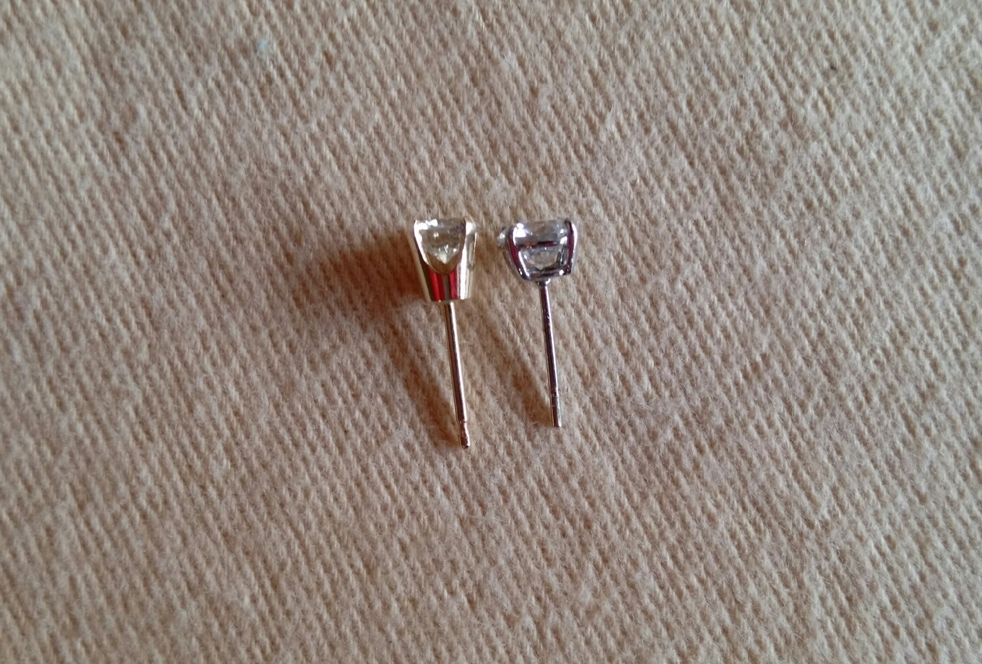 comparison of high vs low diamond mountings: the yellow gold earring on the left has a high base. The earring on the right is a low basket mounting.