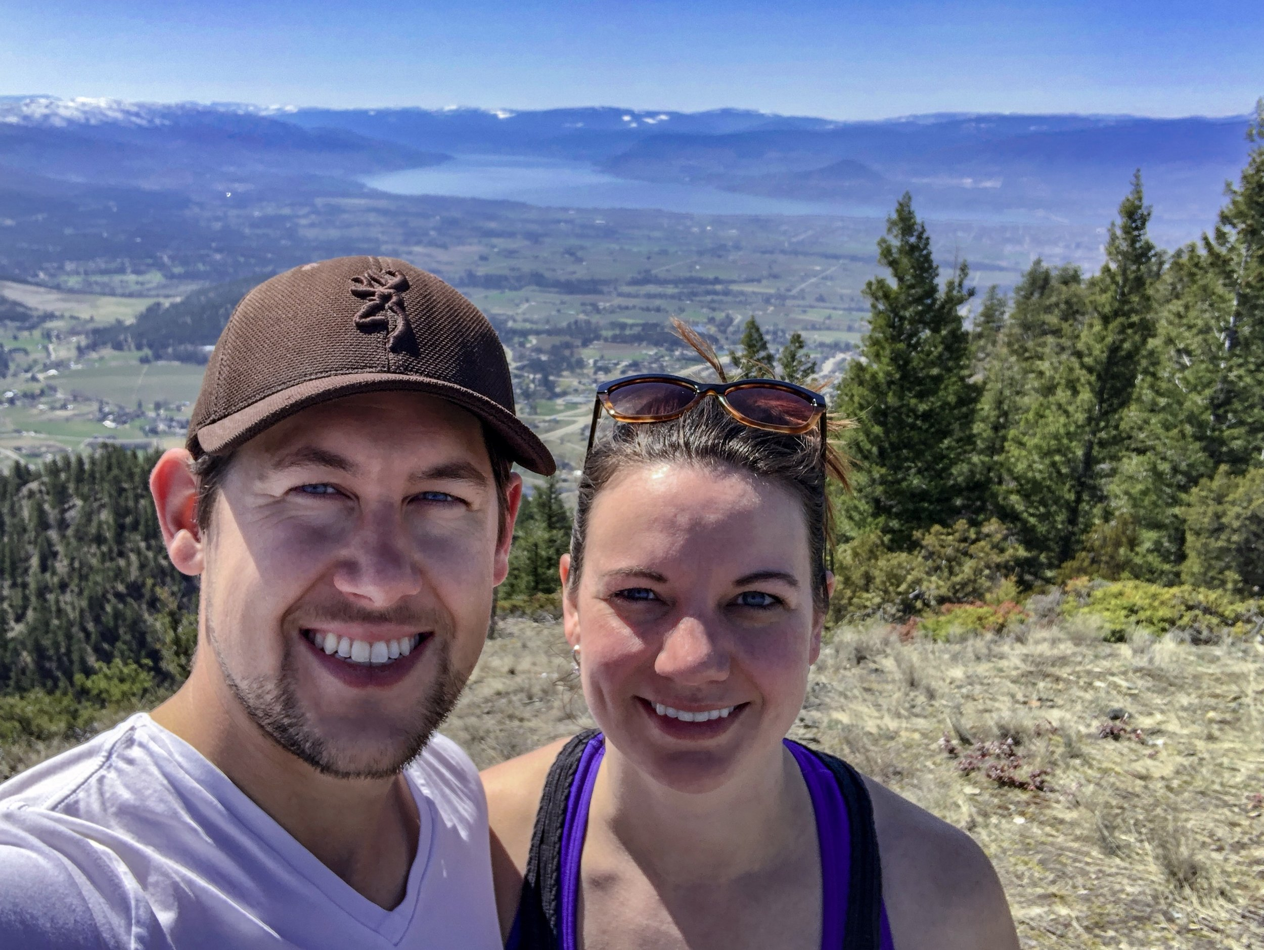 Joshua Elliott and Sarah McIntyre are all smiles after an 11km hike to the top of Black Mountain in Kelowna, BC with views of the Okanagan Valley and Okanagan Lake below.