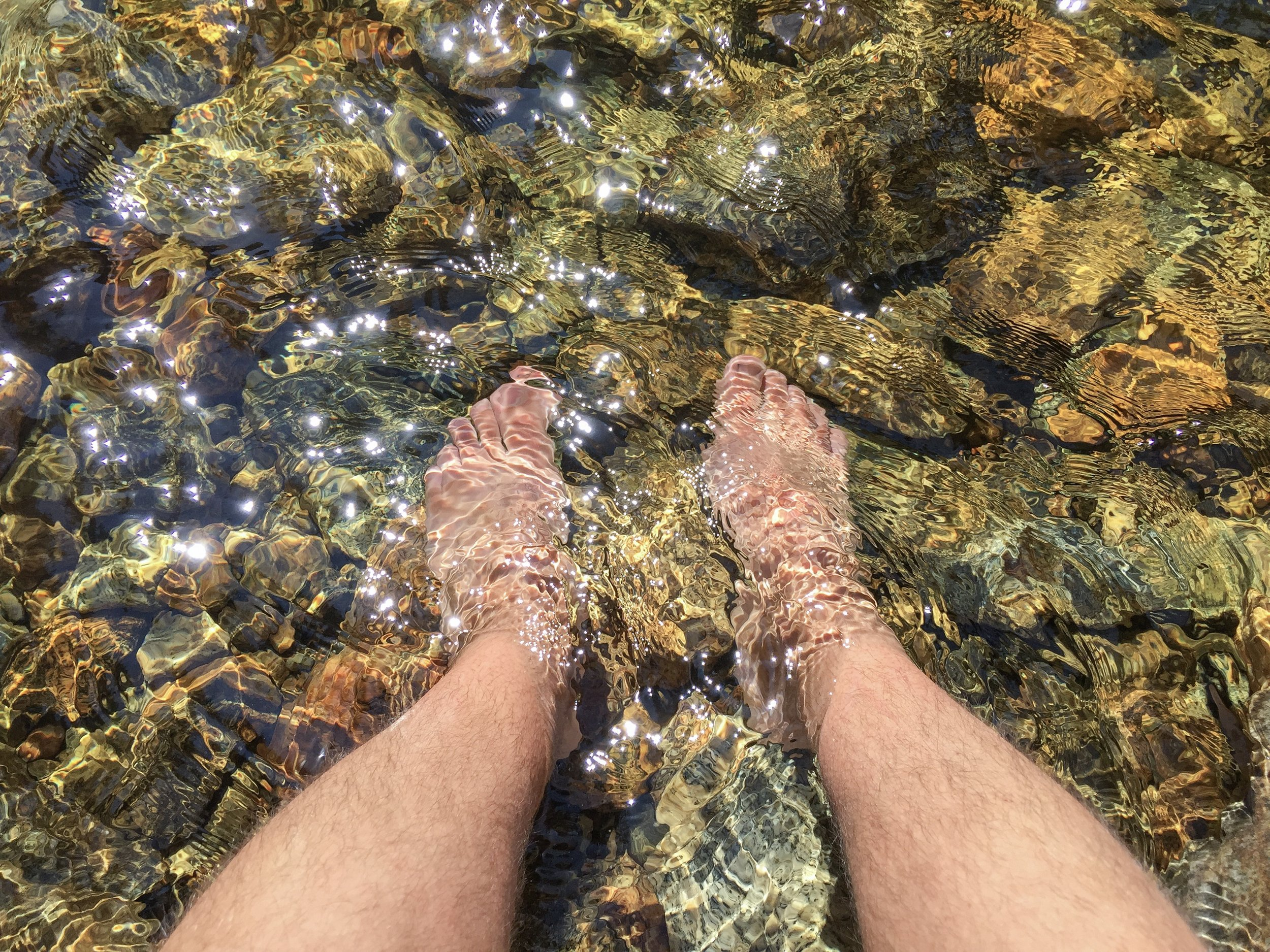 """Kelowna Realtor Joshua Elliott keeping cool with feet in the Bellevue Creek. """"I love that I can work from anywhere."""""""