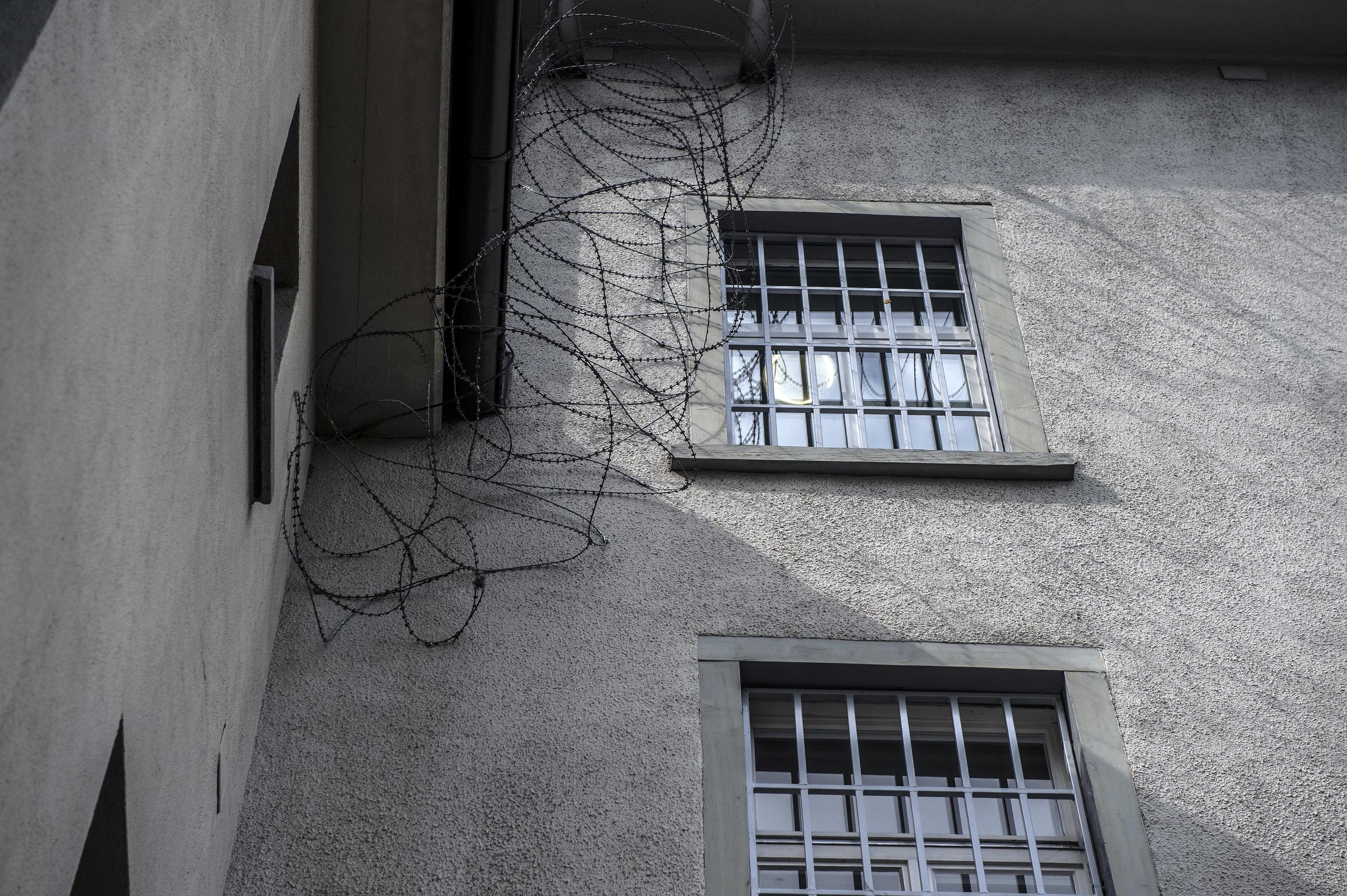 Hohe Sicherheitsvorkehrungen: Die Fenster sind vergittert, über den Mauern ist Nato-Draht gezogen. Ein Drahtrolle, die im Unterschied zum herkömmlichen Stacheldraht mit Klingen besetzt ist.
