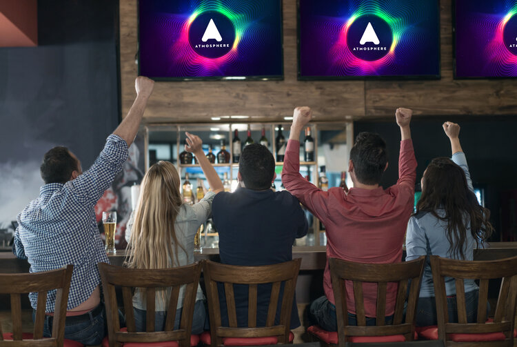 Group of young restaurant patrons watch Atmosphere TV at a bar top.