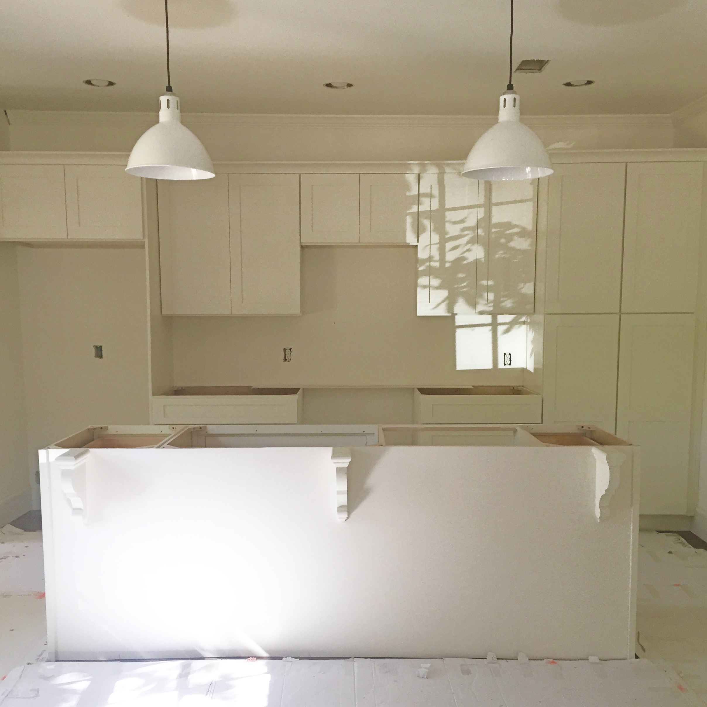 All white kitchen with rustic pendants - subway tile backsplash and marble countertops will complete this space!