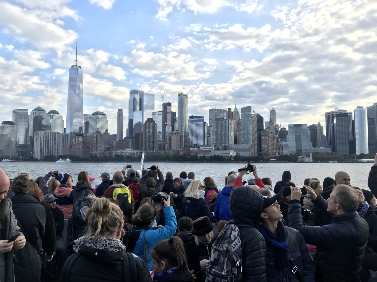 Huddled masses yearning for a good picture of Manhattan, as the boat leaves