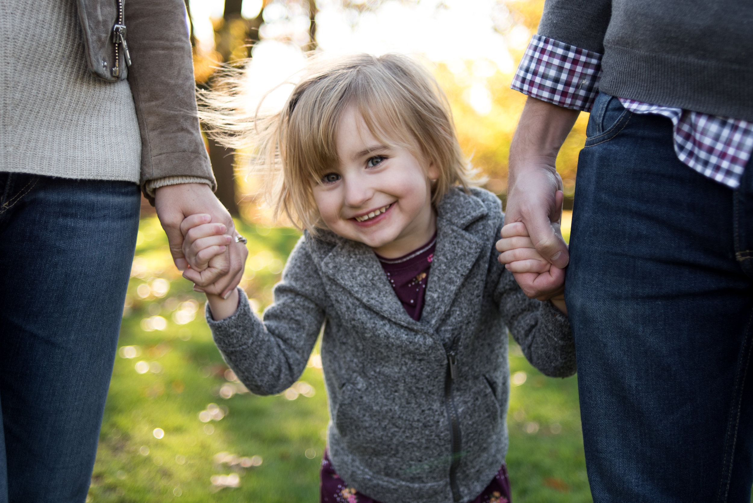 Close up of young girl holding parents hands in Portland park