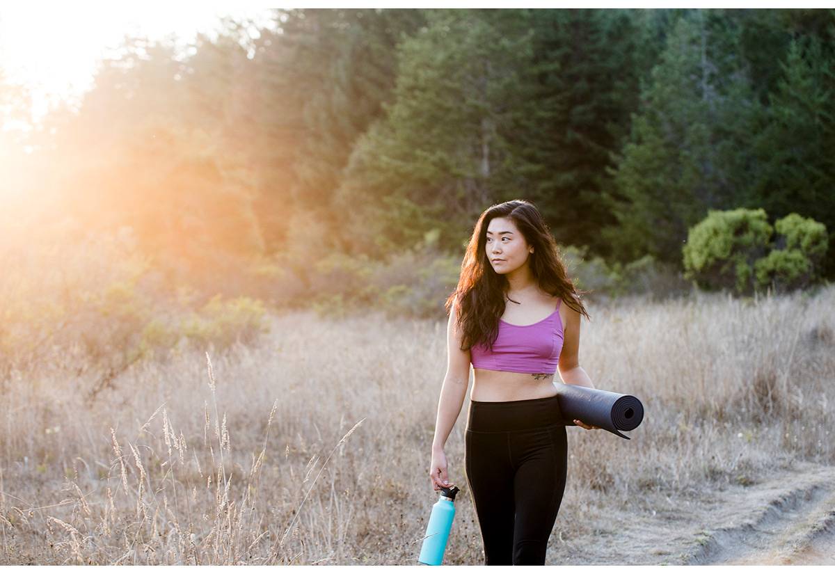 Fitness portrait of woman with yoga mat and water bottle