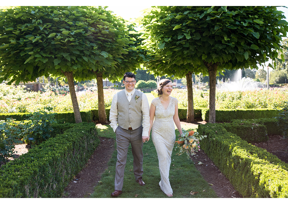 Bride and Groom walking in rose garden in Portland