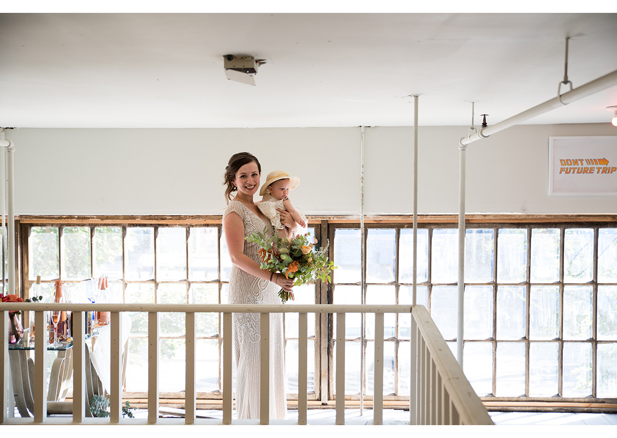 Bride holding daughter before wedding ceremony