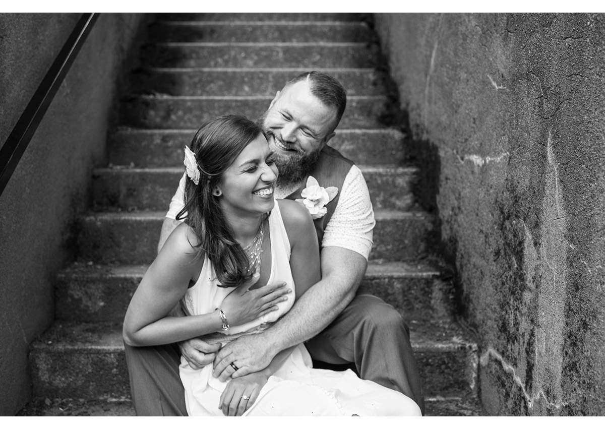 Candid of bride and groom laughing on steps near Pittock Mansion