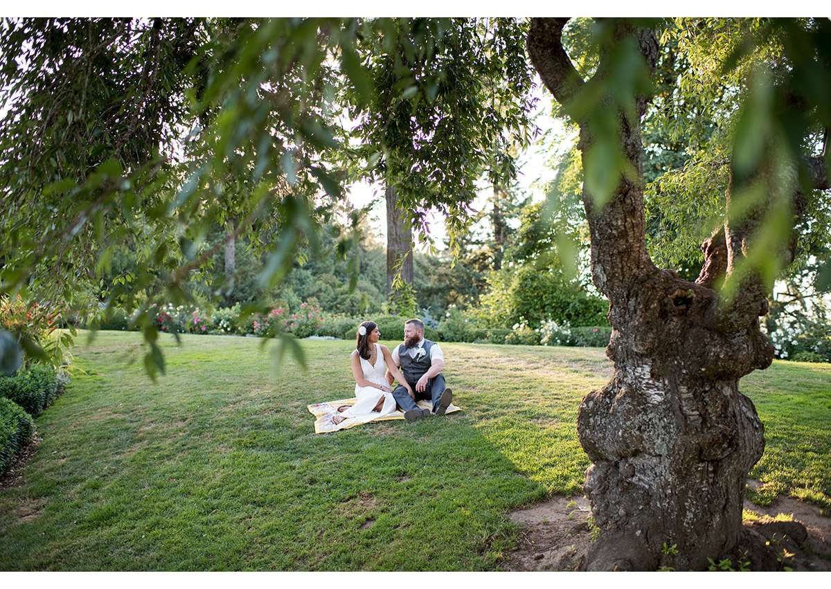 Bride and Groom sitting on lawn at Pittock Mansion