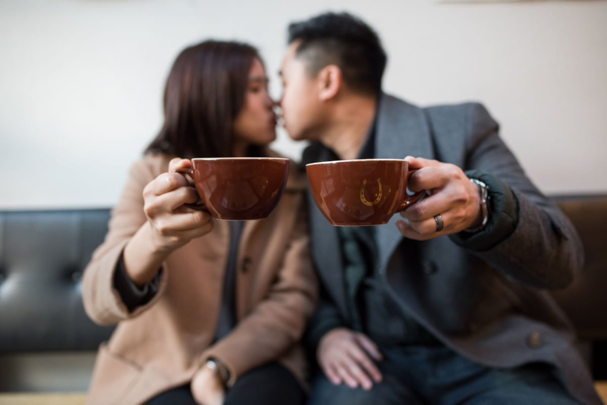 Couple kissing and holding coffee mugs at Stumptown
