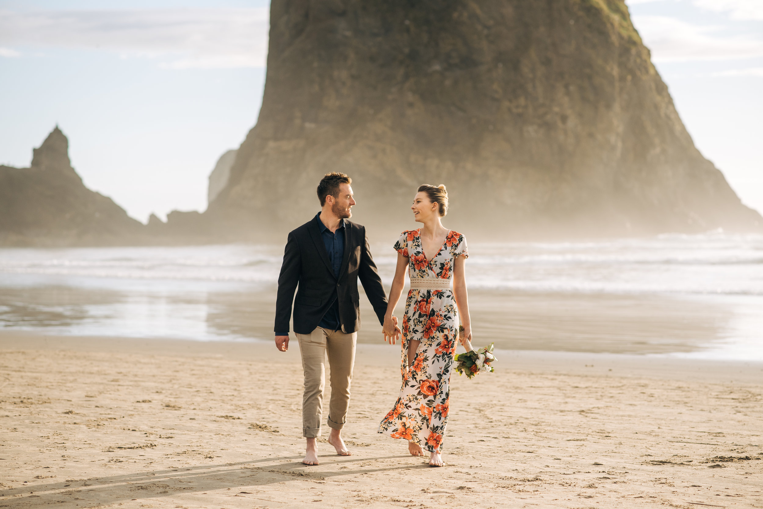 Cannon Beach Elopement couple walking in front of Haystack Rock