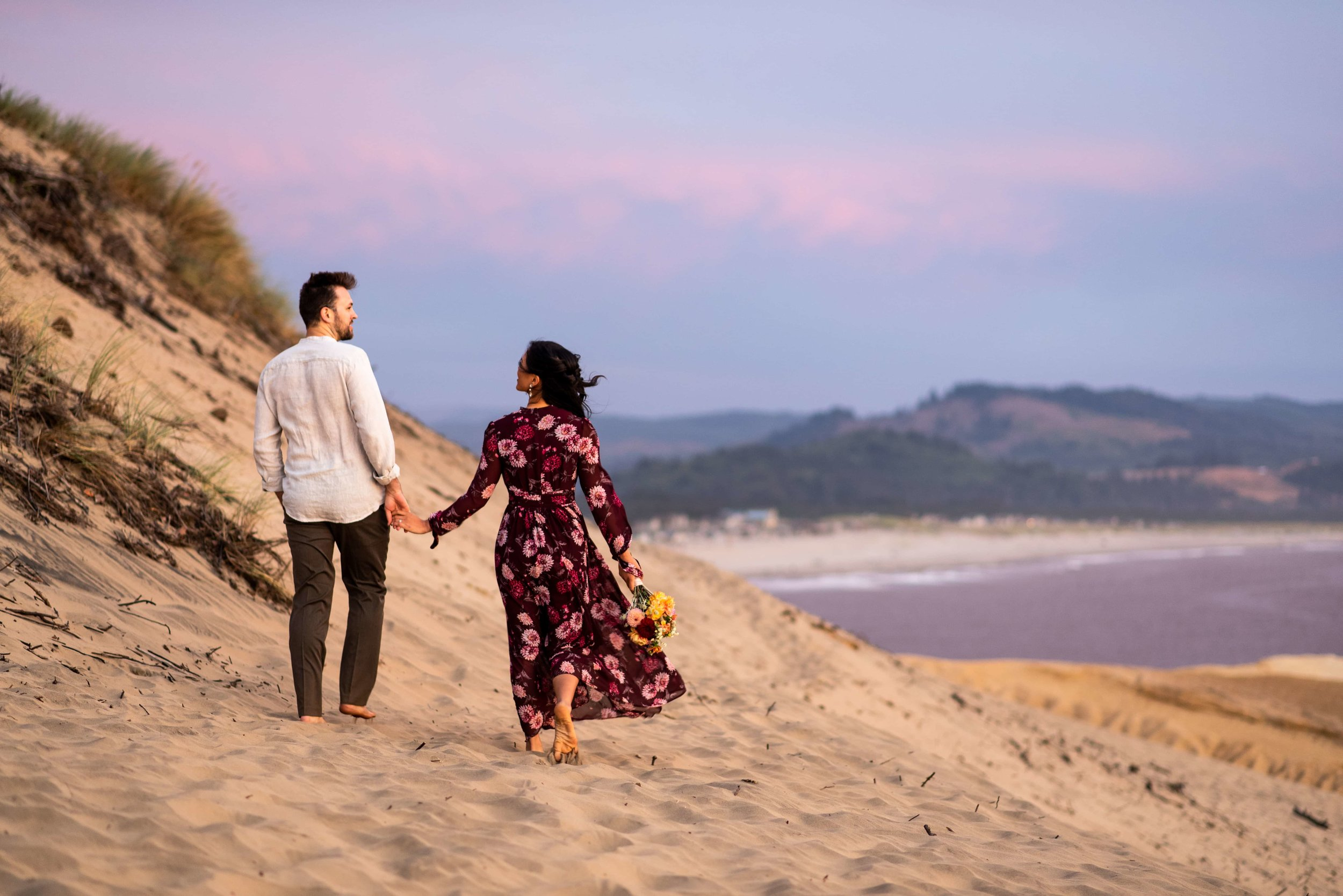 Bride and groom walking in sand in Pacific City
