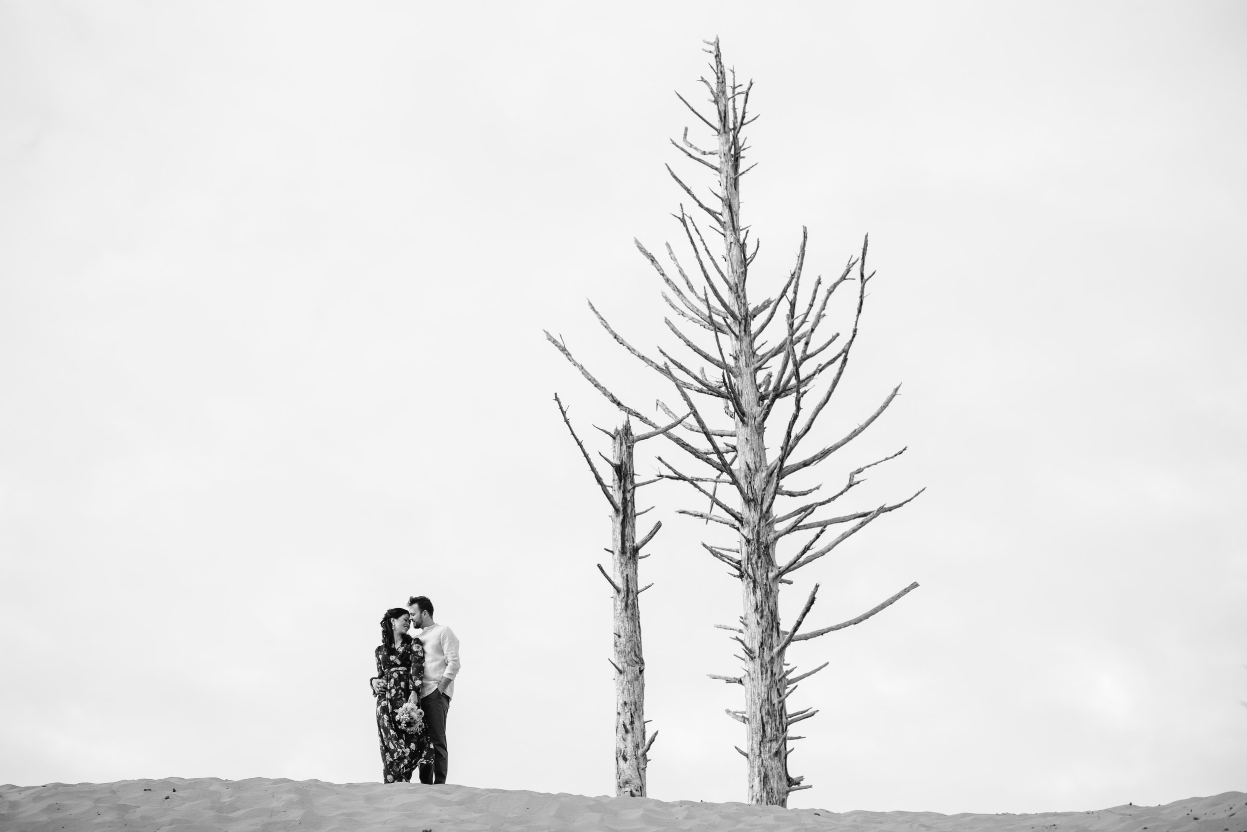 Black and white of couple on top of dune at Cape Kiwanda