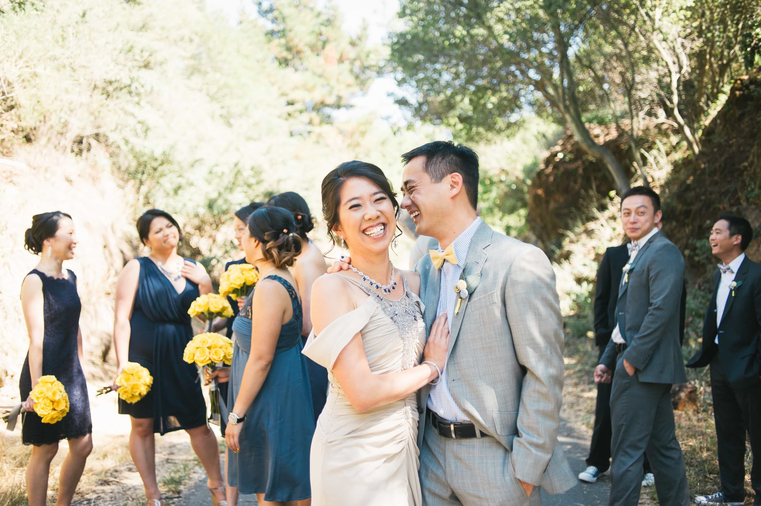 Bride and Groom laughing with wedding party behind them