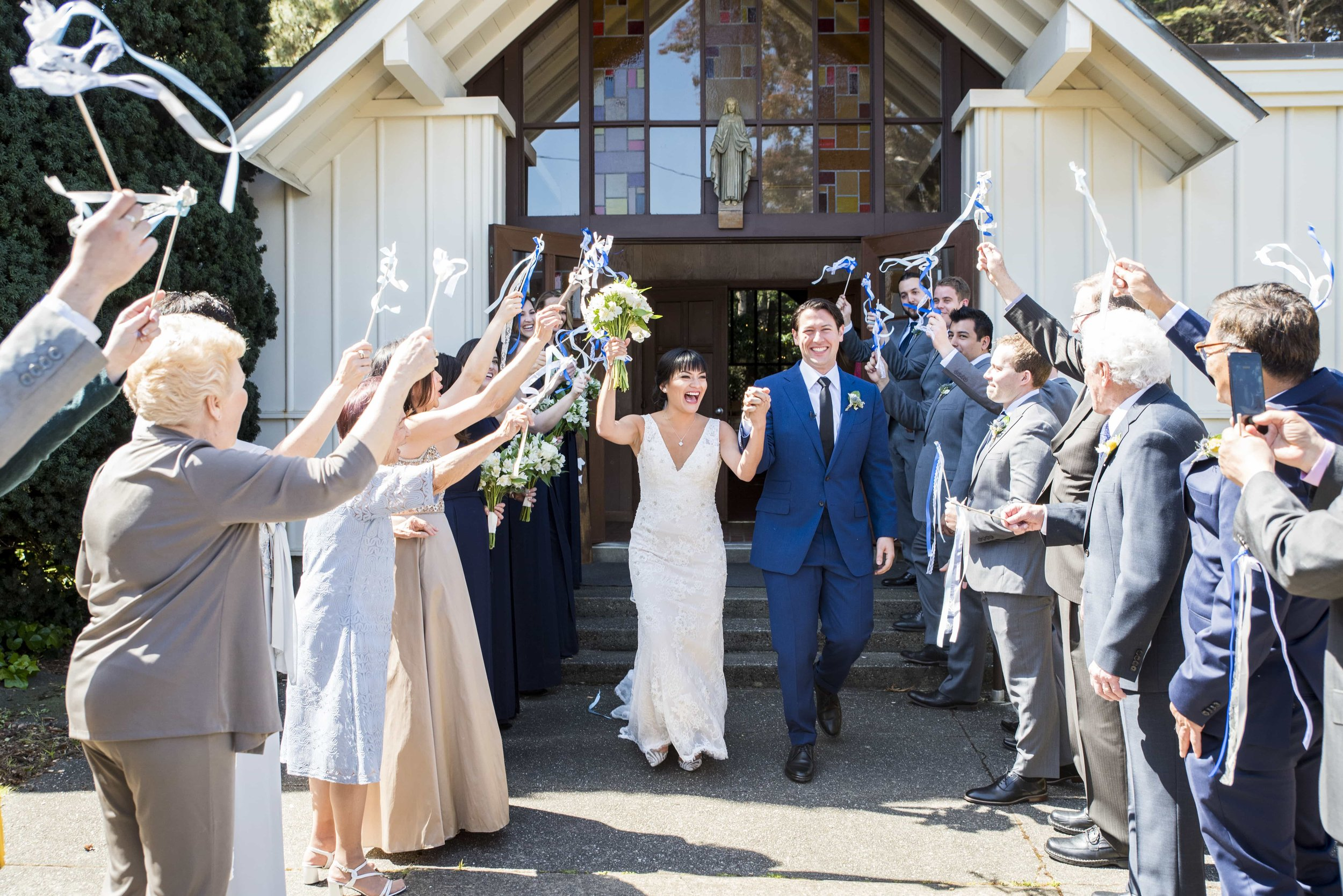 Bride and Groom exiting historic church as guests wave streamers
