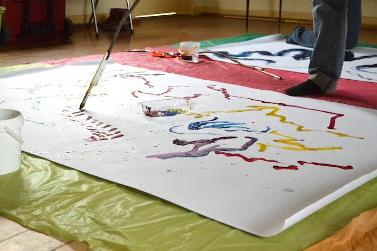 Participant painting to music using paintbrush attach to stick on a big piece of paper. A variety of marks appear on the paper including short red vertical lines; yellow, red, blue purple squiggly lines & small dots made in a variety of colours scattered around line work.  © all images by   Natalya Garden-Thompson, 2016