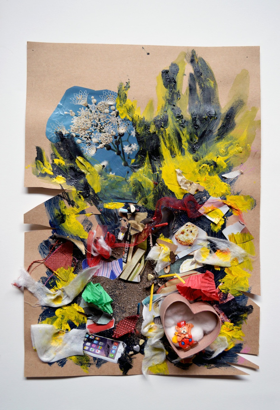 Natalya Garden-Thompson,  Resilience in the Chaos , 2017, Pastel, acrylic, sand, dirt, magazine images, badge & cotton wool, 4 x 30 x 42.5 cm  Photographed of a three dimensional artwork on brown cardboard with thick black, blue & yellow paint applied expressively. There are bits of unpainted cardboard around the edges. Stuck on top of the paint are collaged pieces of: dirt, sand, small pieces of blue & yellow wood, pieces of torn up tissue, wool, material, magazines clippings (including an image of an IPhone, flowers, bits of food), muffin wrappers and a small cardboard heart shaped box full of cotton wool with a little teddy bear wearing red and blue overalls and a red hat who is carrying a small yellow bag on a stick over his shoulder. He is waving. The cardboard has triangle shapes cut out of it on the middle left hand side.