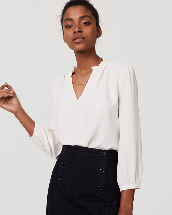 A plain white or cream blouse is a great option. Neutral colors suggest a softer more friendly personality. This particular blouse if from the Loft. You can purchase it  here .