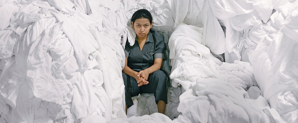 """MEXICO:  The Chambermaid  /  La camarista   A film by Lila Avilés  One of the best reviewed films of the year—currently number three in Rotten Tomatoes' list of best films of the year—Lila Avilés' acclaimed debut feature is a poignant and delicate class portrait.  The Chambermaid  follows Eve — played by the wonderful Gabriela Cartol—a young chambermaid working in one of the most luxurious hotels in Mexico City, an exclusive glass tower inhabited by wealthy guests whose lives she imagines by their belongings left behind and their absences.  Long, laborious shifts prevent Eve from caring for her child as she helps guests with their own children, but she believes she can better her situation after she's promoted to work at executive-level suites, for which she accepts a grueling schedule. In keeping with her desire to improve her lot, she simultaneously enrolls in the hotel's adult education program.  An incipient friendship with her coworker and an awkward, silent flirtation with a window-washer prod her toward much needed bravery. When things don't turn out as planned, Eve transforms her solitary explorations and newfound courage into the strength to face a life outside the high-class prison that's entrapped her, breaking rules and discovering herself.  Inspired by Avilés' theater play of the same name — in turn inspired by Sophie Calle's 1980 artistic project """"The Hotel,"""" in which the French artist worked as a chambermaid in a Venice hotel— The Chambermaid  is a standout among a thriving new generation of Mexican and Latin American female filmmakers. With impeccable cinematography, a near-documentary eye, and a humanistic gaze, the film signals Avilés as a talent to watch."""