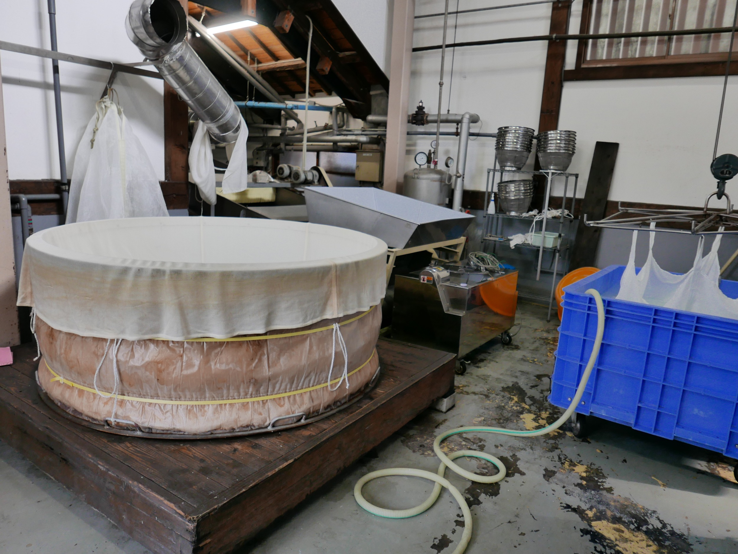 The polished rice is rinsed in large bags as on the right or in the stainless sieves (for traditional and high quality sake,) and then steamed in the huge spa bath looking vessel on the left. Several batches are steamed at once.