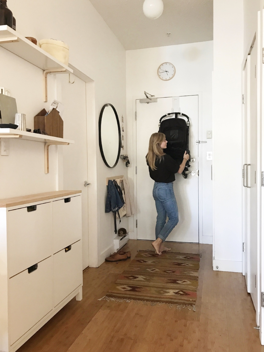 """I can't remember if I am putting away the stroller or taking it down but I thought it would be helpful to have me in the picture for scale to show how small our entry way is. But then I realized at 5'2"""" it might have been more helpful to have a more normal sized person in the photo...whoops!"""