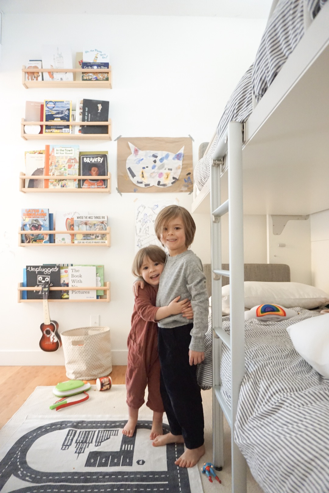 The kids in their small shared bedroom standing beside their wall bunk beds with their library carrying up the wall.