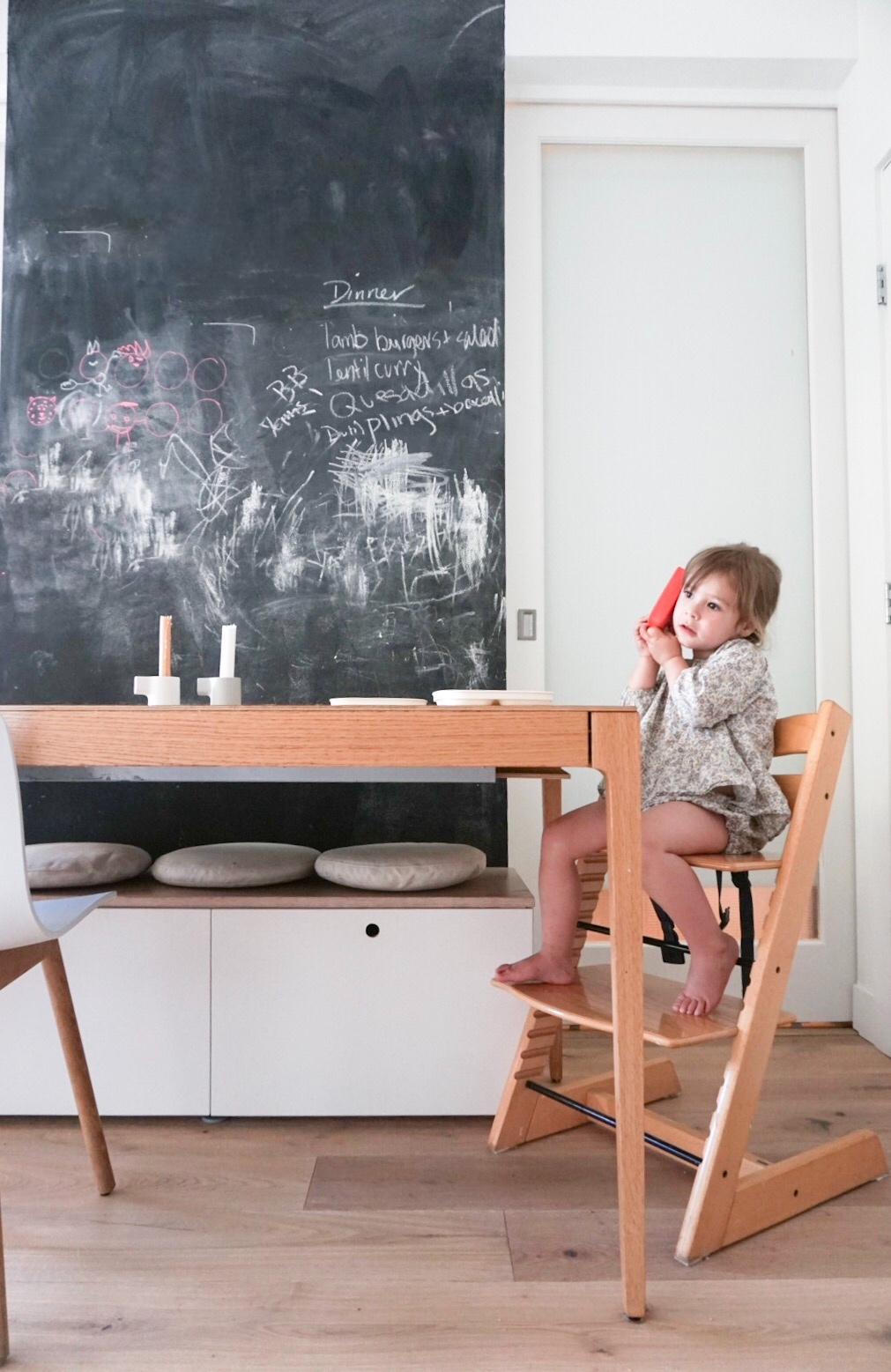 Mae on the phone  (in PV ), in our second-hand Stokke Tripp Trapp, Ikea Storage Bench in the background