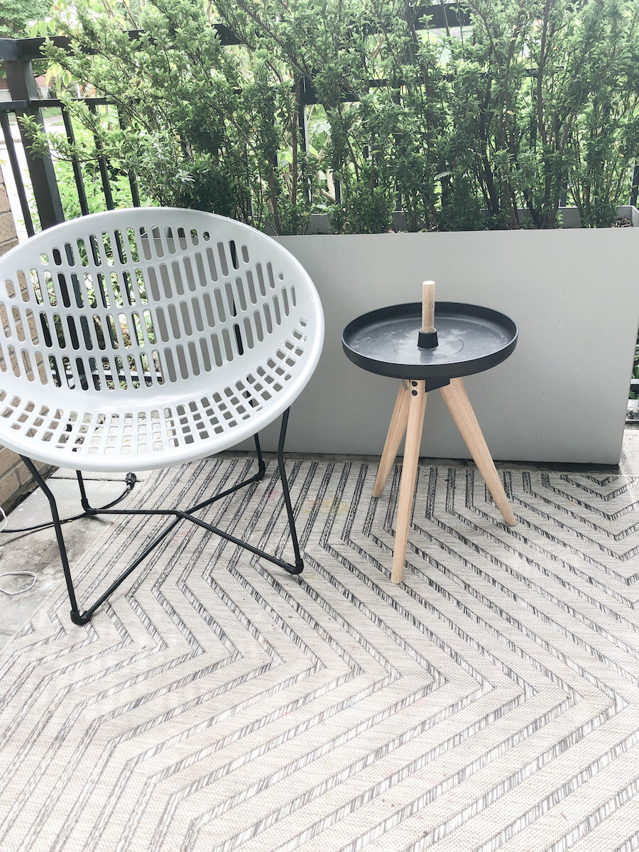 Solair chair and side table borrowed from inside. Narrow planters to provide plant screening to the sidewalk.