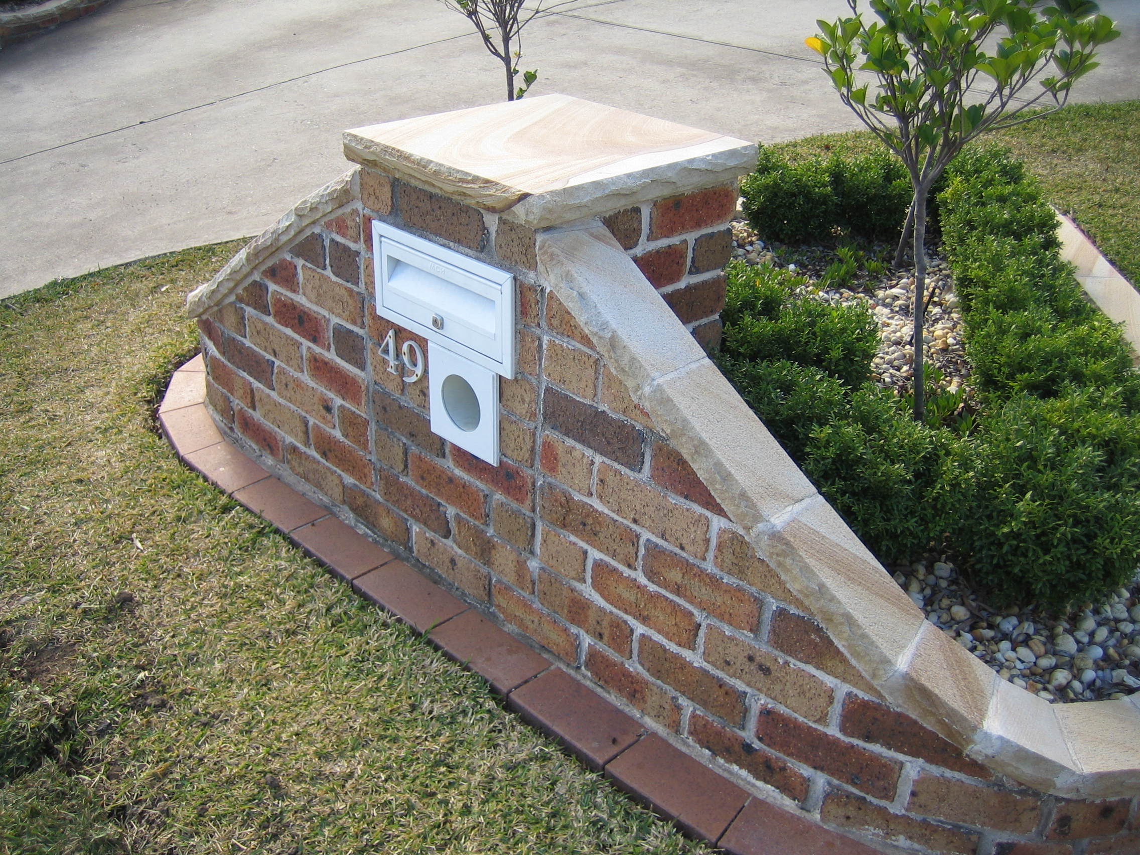 062 sandstone cupping on top of the letterbox and brick wall.jpg