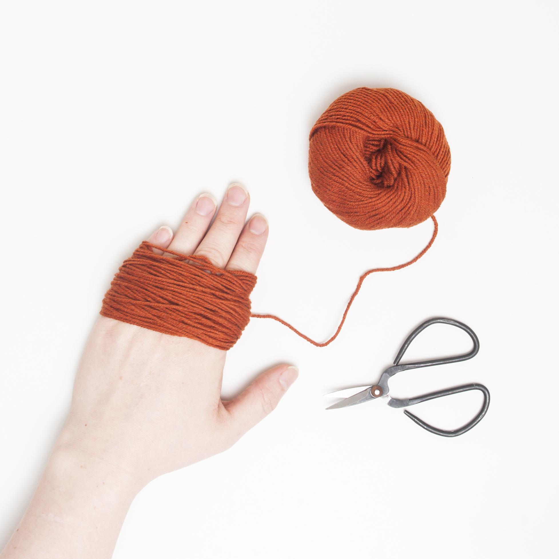 Først trenger du mange små trådbiter i lik lengde - surr garnet rundt hånda, telefonen eller en fyrstikkeske, og klipp opp den ene siden.