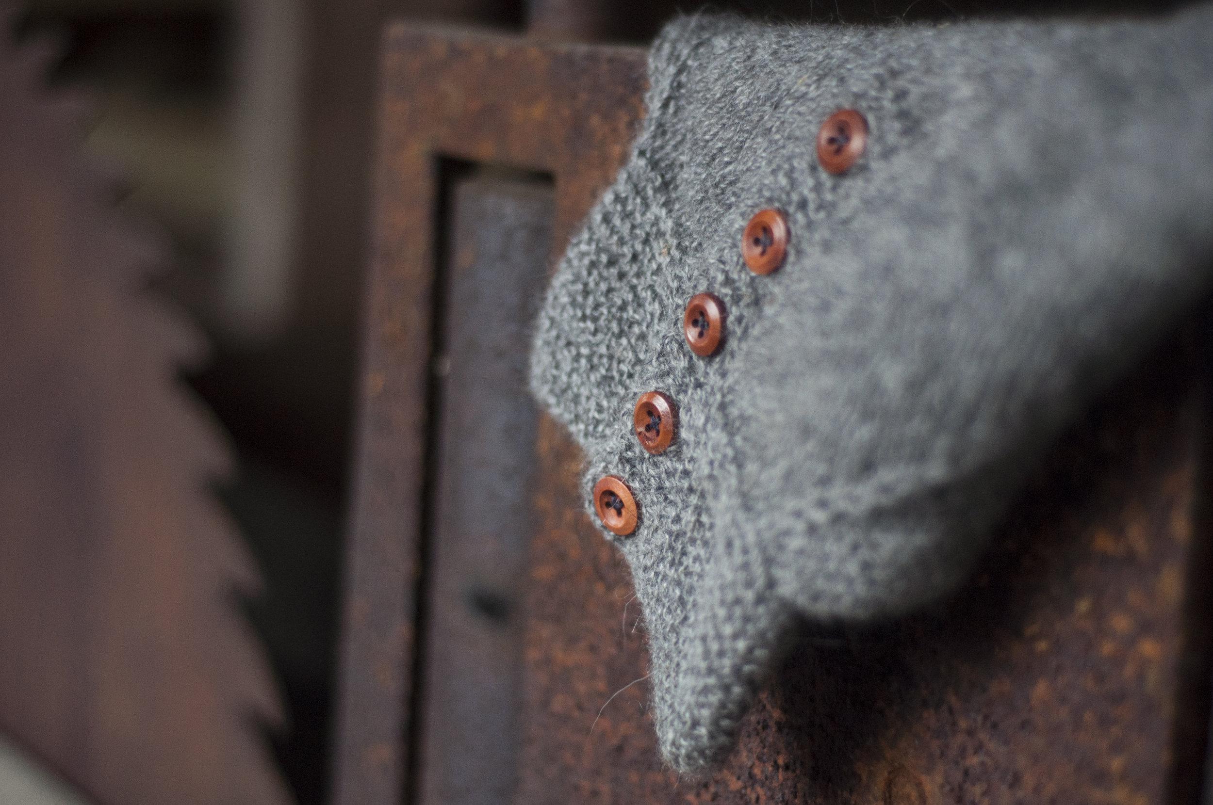 Røff saueull, treknapper, rust og sagtenner. Treknappene plukker opp fargen i rusten og strukturene skaper en interessant kontrast.