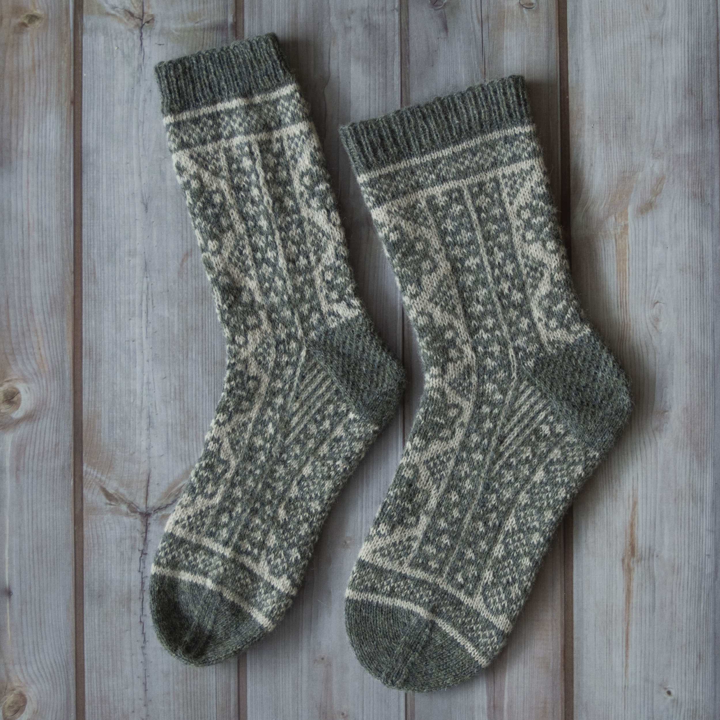 Begge sokkene er skylt opp og tørket, til venstre flatt og til høyre på  sokkeblokker.   Ned til hælen er de strikket samtidig på magic loop så sidene var identiske før oppskyll.