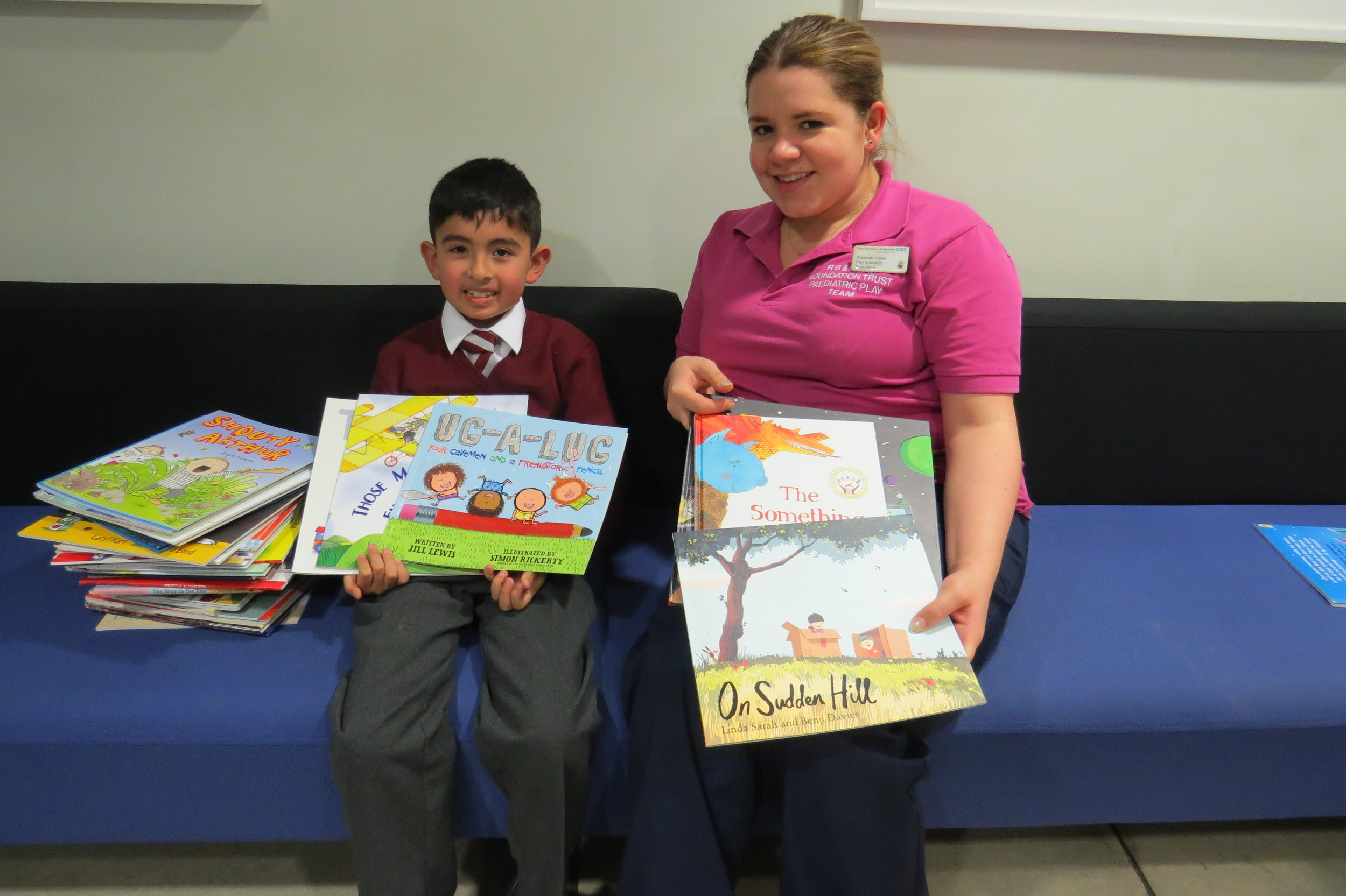 Luis Fafian and Liz Grewe, play therapist at the Royal Brompton Hospital, enjoy exploring the cardiac clinic's new shipment of children's books donated by Oscar's Book Prize.