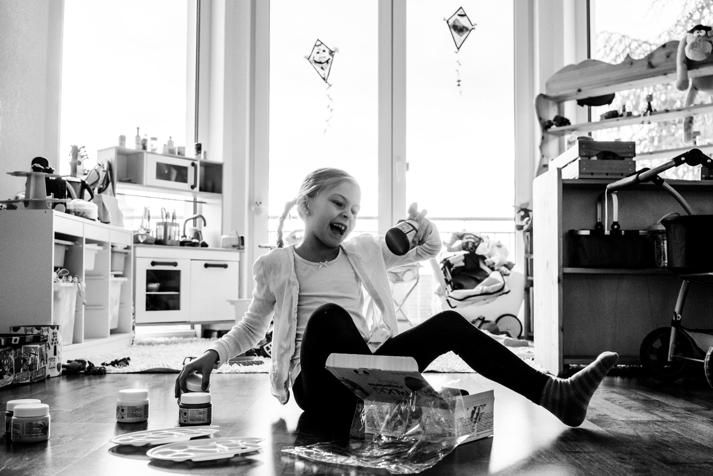 Eines meiner liebsten Familienfotos aus einer Familienreportage - Porträt eines Mädchens, das drinnen auf dem Boden sitzt