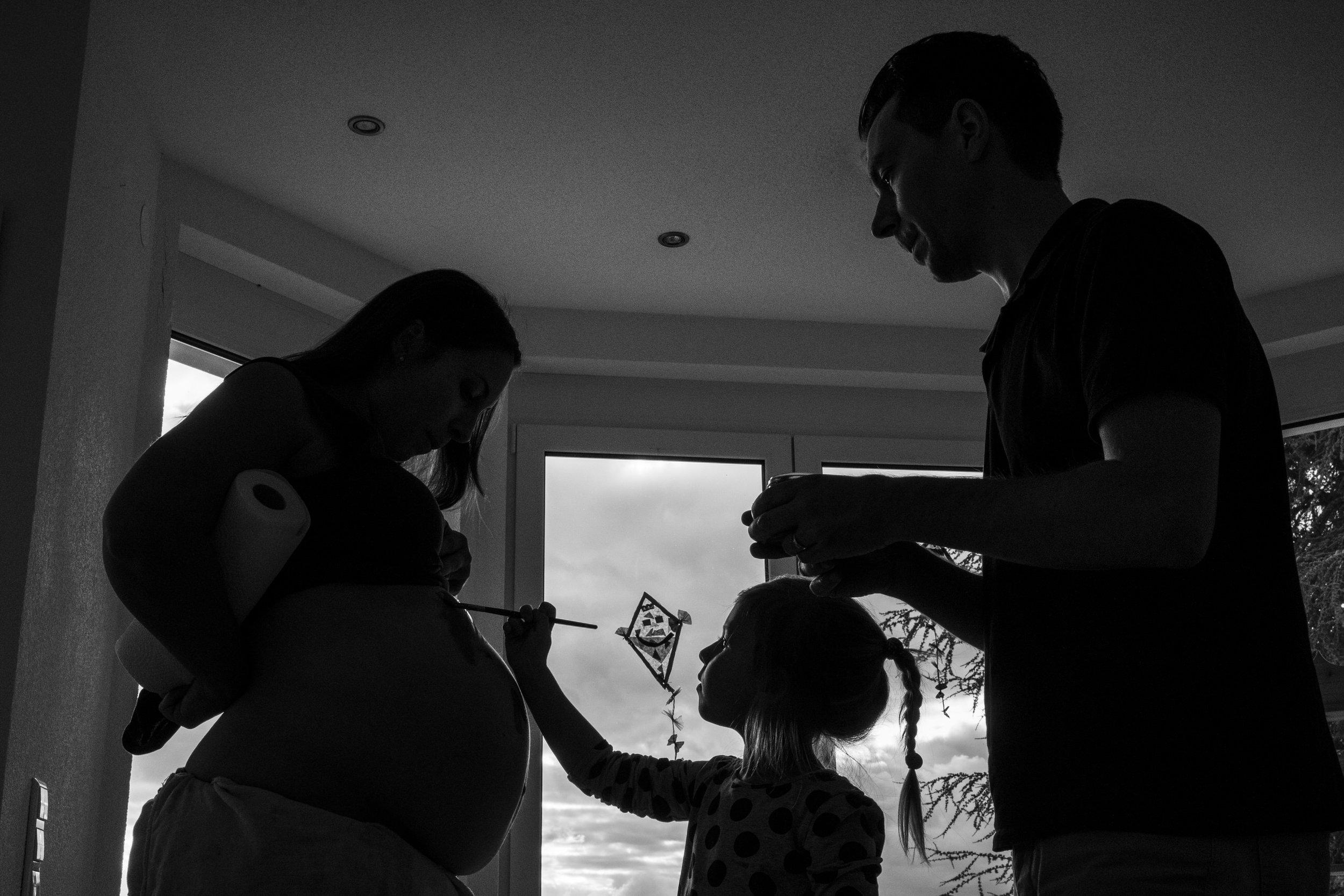 Eines meiner liebsten Babybauchfotos aus einer meiner Familienreportagen - Mädchen bemalt drinnen den Babybauch ihrer Mama