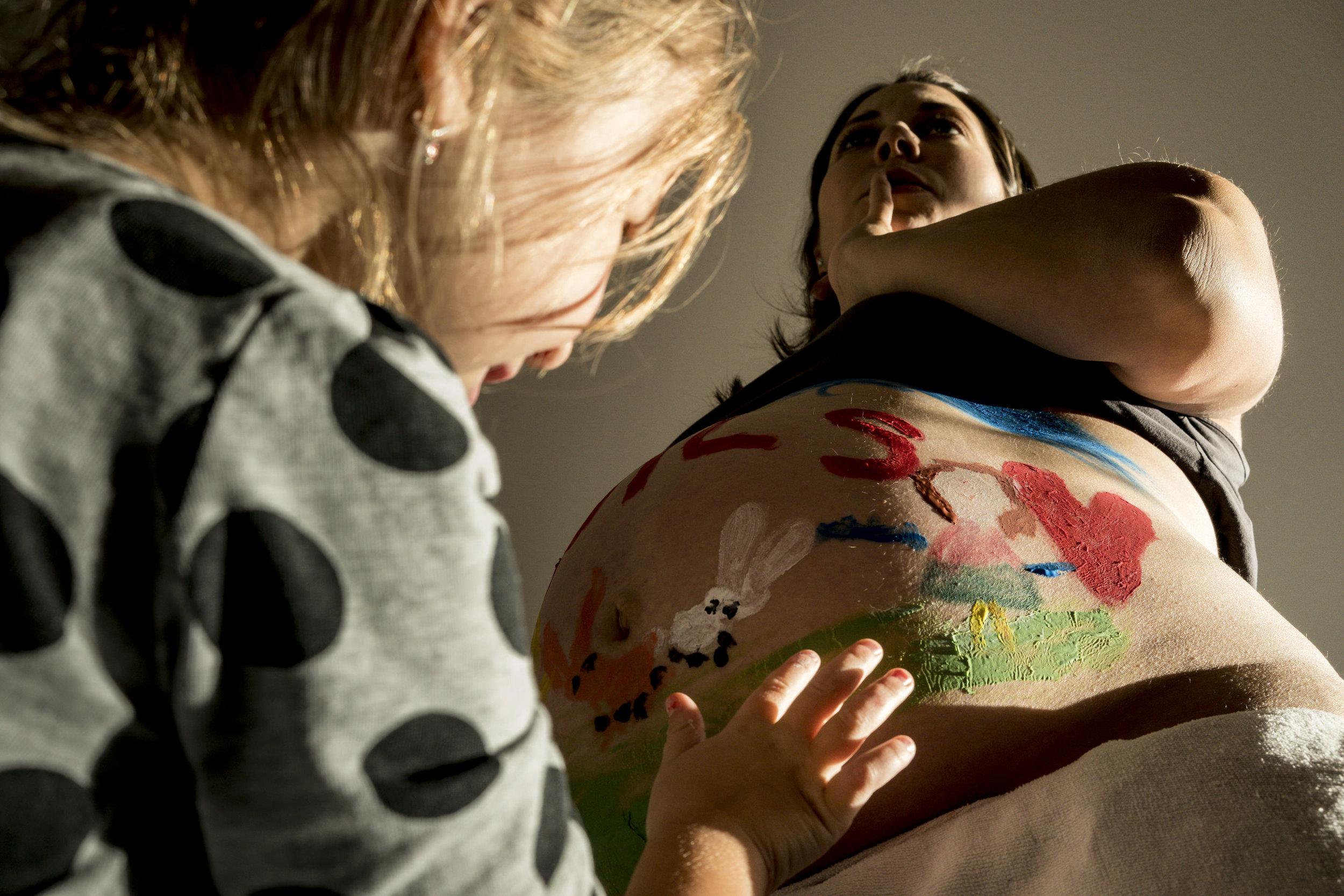 Eines meiner besten Babybauchfotos - Tochter bemalt drinnen den Bauch ihrer glücklichen, schwangeren Mama