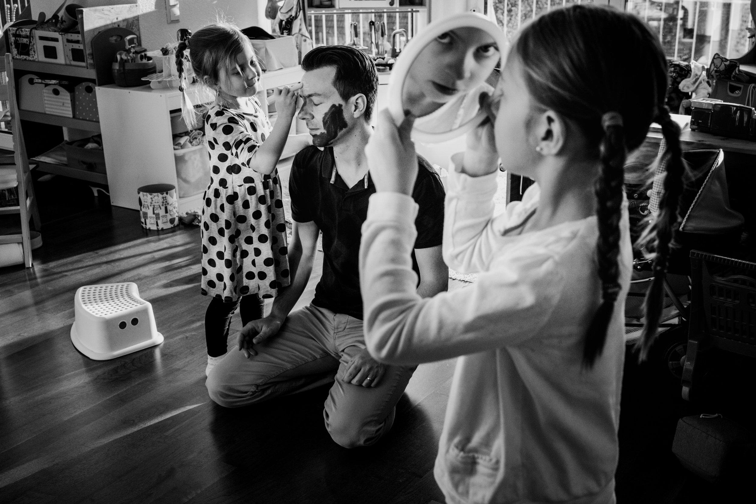 Eines meiner besten Familienfotos aus einer Familienreportage, Tochter schminkt Papa im Gesicht, andere Tochter betrachtet sich im Spiegel