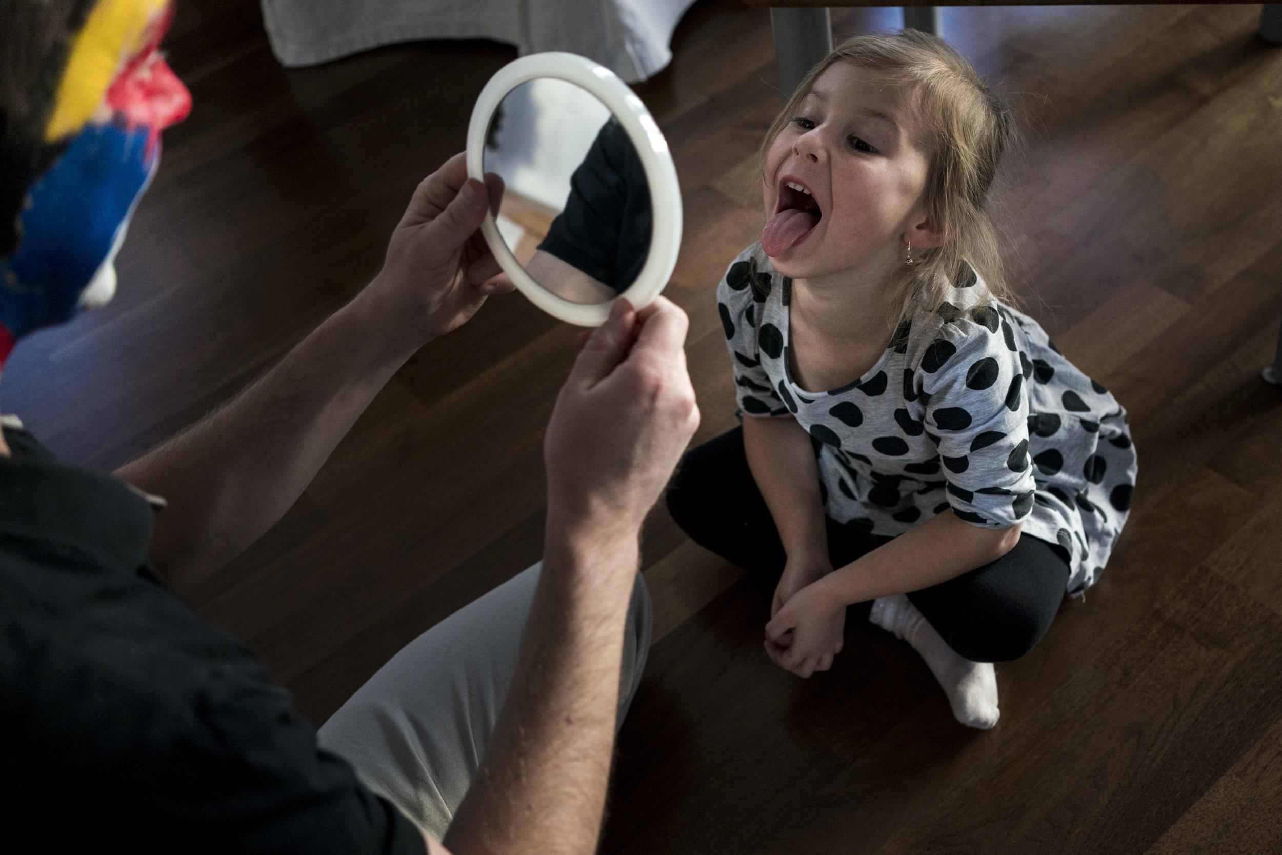 Eines meiner liebsten Familienfotos aus einer Familienreportage - Mädchen schaut sich im Spiegel an und streckt die Zunge raus