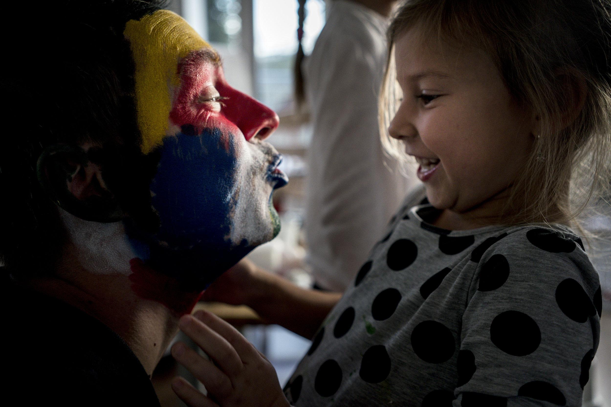 Eines meiner liebsten Familienfotos aus einer Familienreportage - geschminkter Papa zeigt Tochter einen Kussmund